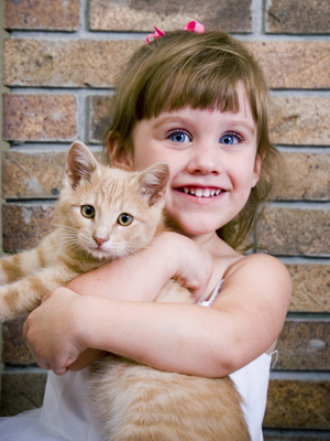 two year-old girl holding a kitten.